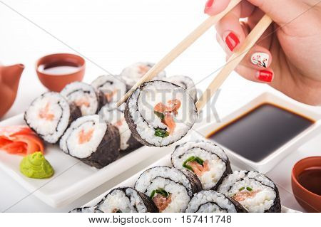 woman hold sushi roll on a background