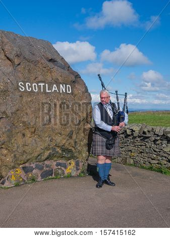 CARTER BAR, SCOTLAND-16 SEPT. 2016: Traditional Scottish babgpiper plays at Carter Bar border crossing along the A68 welcoming visitors to. Bagpipe players are one of the symbols of Scotland