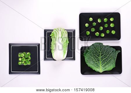 different types of cabbage - the Brussels Savoy and Beijing cabbage lie on plates black color
