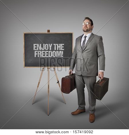 Enjoy the freedom text on blackboard with businessman carrying suitcases