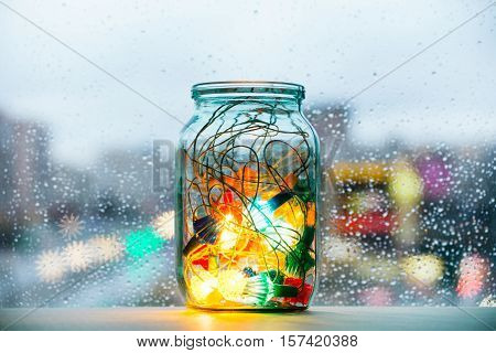 burning garland in a glass jar against the window with raindrops