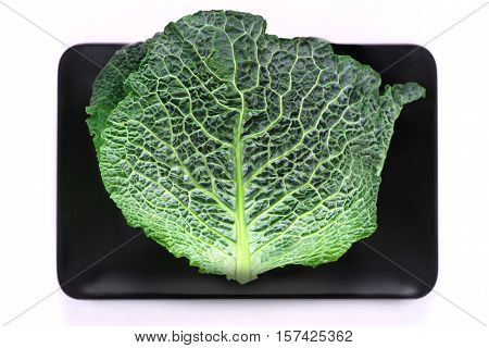 Savoy cabbage lie on rectangular plates black color