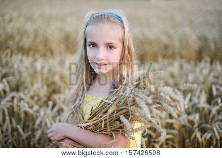 portrait of beautiful girl holding sheaf of wheat