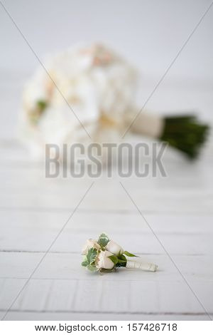 Wedding bouquet of orchids and boutonniere on white background.