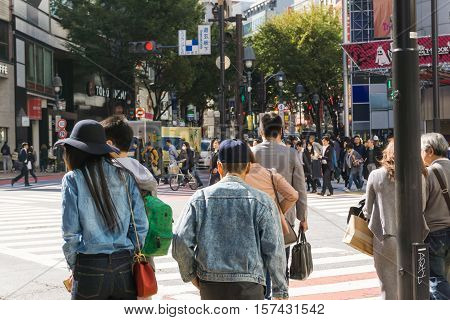 TOKYO - OCTOBER 24: Pedestrians at Shibuya crossing October 24 2016 in Tokyo JP. The famed crossing is one of the most well known examples of a scramble crosswalk.