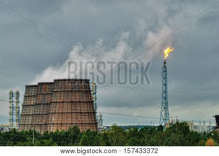 Tobolsk, Russia - July 15. 2016: Sibur company. Torches for burning of associated gas of Petrochemical Industrial Complex and water-cooling towers of combined heat and power plant