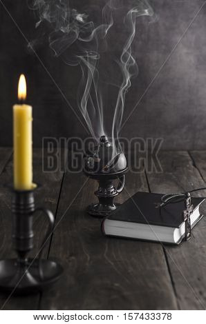 Antique candlestick and burning candle and in the background a incense holder