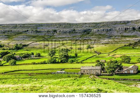 Farm house in green fields of the Yorkshire Dales near Ingleton, England on sunny day.