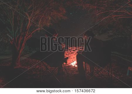 Couple sitting at burning camp fire in the night. Camping in the forest under starry sky Namibia Africa. Summer adventures and exploration in the african National Parks. Selective focus on fire. Toned image.