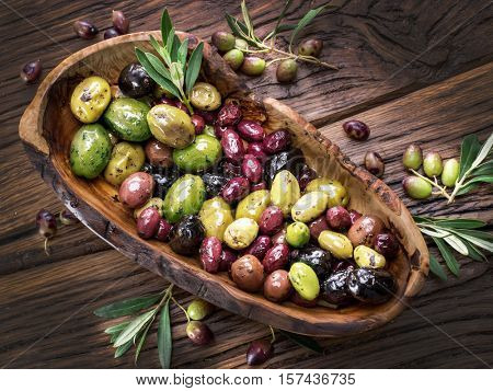 Whole table olives in the wooden bowl on the table.