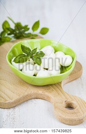 Mozzarella In A Green Plate On A Wooden Table. Delicious Fresh Cheese With Basil Leaves On A Wooden
