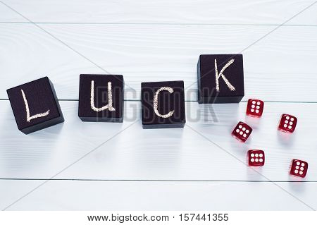 Luck word written in black wooden cubes and red dice on a blue wooden background flat lay. Concept for business risk chance good luck or gambling top view.
