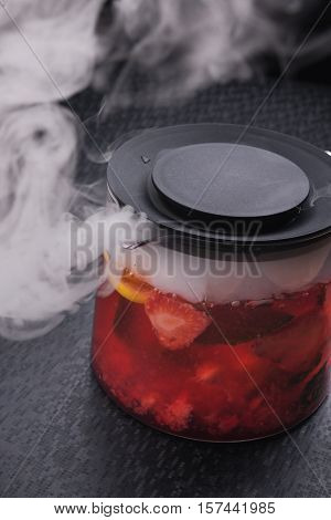 strawberry tea in teapot with fume on on black background