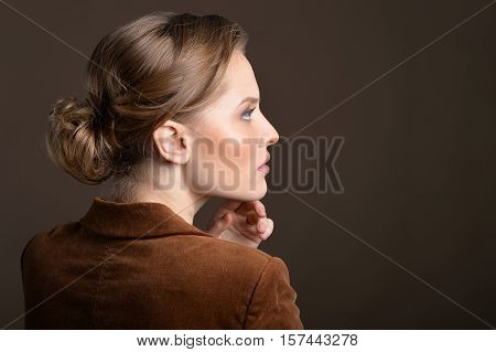 Side view portrait of young woman looking at the distance against grey background