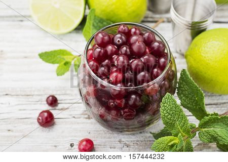 Ingredients for cranberry mojito with fresh cranberries, mint flavored, juicy lime and ice cubes for seasonal Family beverage on a light wooden background. selective focus