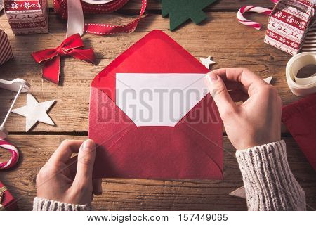 red envelope with postcard  in female hands. christmas background