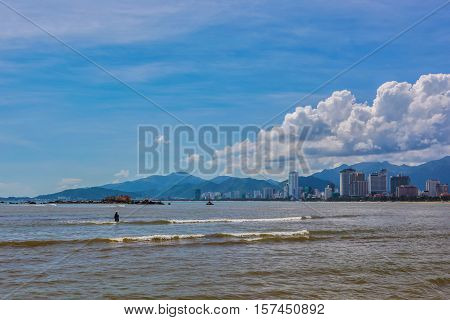 A view of Nha Trang bay Vietnam on a beautiful day with a single fisherman.