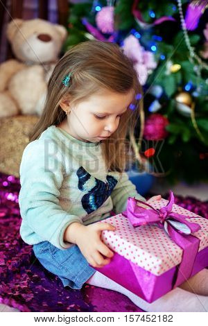 beautiful baby opens a gift. The concept of Christmas and a happy new year.