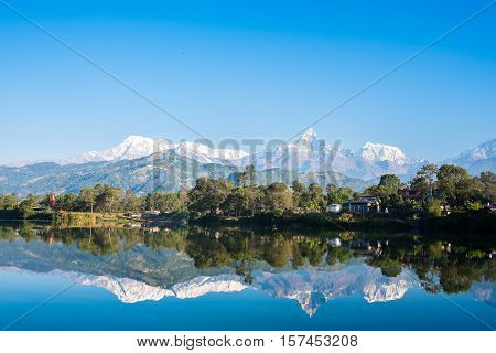 Lake Phewa in Pokhara, Nepal, with the Himalayan mountains in the background, including Machhapuchhre and Annapurna