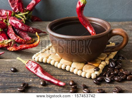 black coffee with pepper spicy. wooden background.