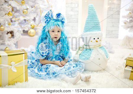 Beautiful little girl with blue hair and blue bow and wearing a blue dress sitting in a New Year's interior