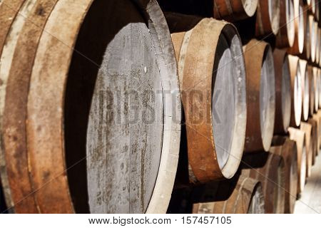 Closeup View Of Oak Barrels Stacked In The Old Cellar With Aging Port Wine