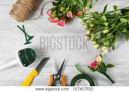 Beautiful flowers and florist equipment on white wooden background