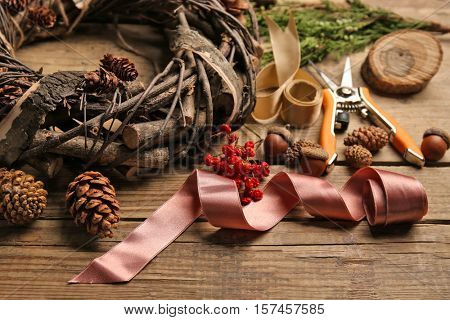 Decorative wreath and florist equipment on wooden background