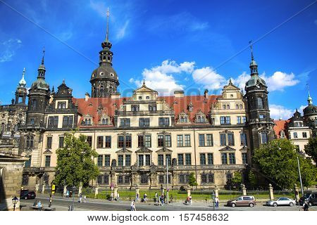 DRESDEN GERMANY - AUGUST 13 2016: Tourists walk on Sophienstrasse street and majestic view on Saxony Dresden Castle (Residenzschloss) in Dresden State of Saxony Germany on August 13 2016.