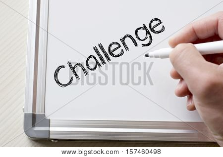 Human hand writing challenge on whiteboard over wooden background