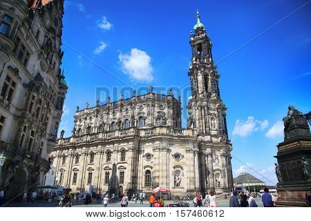 DRESDEN GERMANY - AUGUST 13 2016: Tourists walk and visit on Schlossplatz majestic view on Katholische Hofkirche in Dresden State of Saxony Germany on August 13 2016.