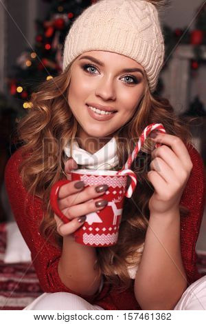 Charming Woman With Curly Hair In Warm Cozy Winter Clothes Posing Near Christmas Tree