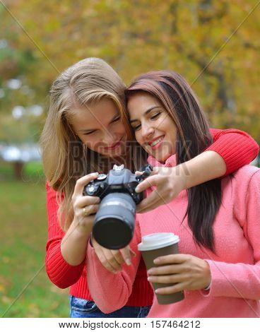 Portrait of two happy female Caucasian friends taking photos with a DSLR camera.