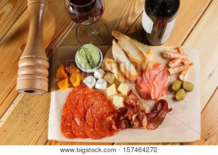 antipasti platter on wooden surface. bottle and glass of wine. different snacks.