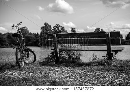 Bicycle near bench and pond in park. Black-white photo.