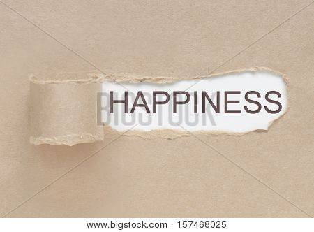 Uncovering happiness, torn paper revealing word underneath