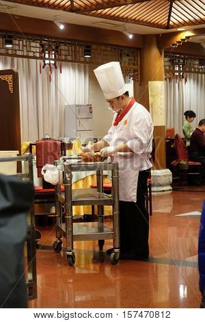 BEIJING - FEBRUARY 22: Cutting peking duck on a plate in the original Quanjude restaurant at the Qianmen street in Beijing, China, February 22, 2016.