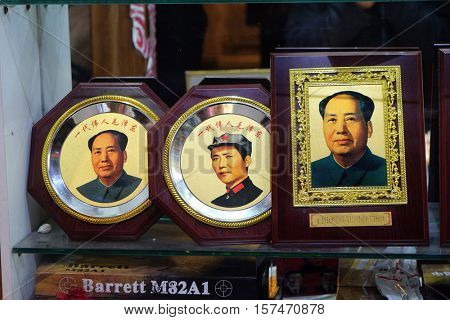 BEIJING - FEBRUARY 24:  Photographs of Chairman Mao Zedong in shop window of pedestrianised shopping area of Wangfujing in Beijing, China, February 24, 2016.