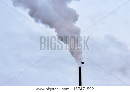 White smoke extending from the chimney in the winter sky
