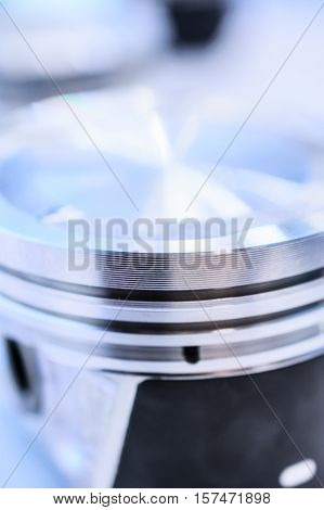Detail of automobile engine piston. Photo closeup, shallow depth of field. Abstract industrial background.