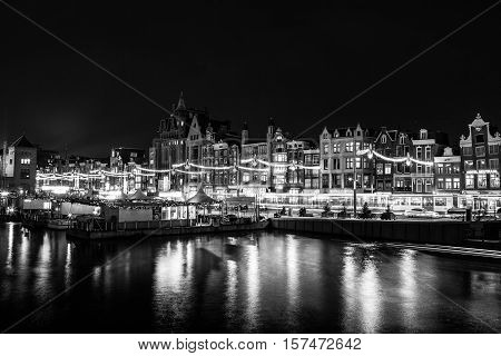 AMSTERDAM NETHERLANDS - DECEMBER 14 2015: Black-white photo of cruise boat moving on night canals of Amsterdam in Amsterdam Netherlands.
