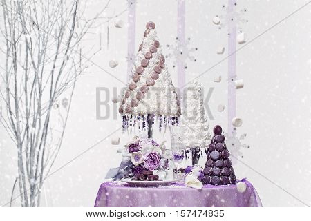 Beautiful set of three handmade white and purple croquembouche wedding cakes made from meringue and macarons standing on small dessert table