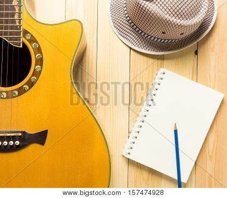 Folk music song writing equipments on wooden table.