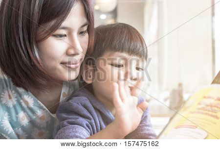 Asian Mother is teaching her son to read a story book