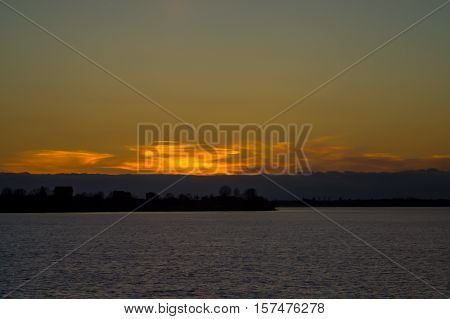 sunset in autumn in November, a bright yellow, brown and black colors, the sun behind horizon, clouds, bright orange heavy different sizes, the dark water of the pond,