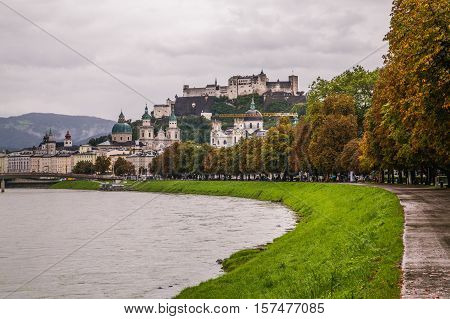 SALZBURG AUSTRIA - 17TH SEPTEMBER 2016: A view along the Salzach River towards Salzburg Old Town in the summer during an overcast day.