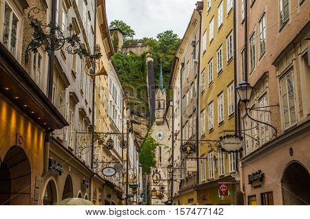 SALZBURG AUSTRIA - 17TH SEPTEMBER 2016: A view along Getreidegasse in Salzburg during the day. The outside of shops and Geistliches Zentrum St. Blasius church can be seen.