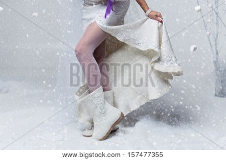 Bride in wedding felted gown. Close-up of female legs in white stockings and wool felted boots. Copy space.