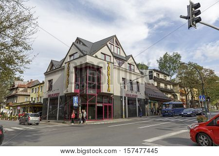 ZAKOPANE POLAND - SEPTEMBER 23 2016: Residential building with storefront that is at the crossroads. Several people are waiting for the green light to pass to the other side of the street