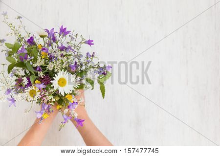 Beautiful bunch of wild flowers in woman's hands on the white wooden background. Flowers from the park. Summer. Gift bouquet.